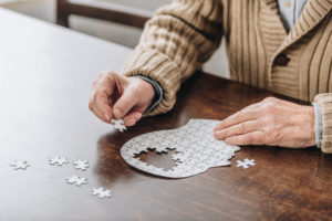 cropped view of senior man playing with puzzles