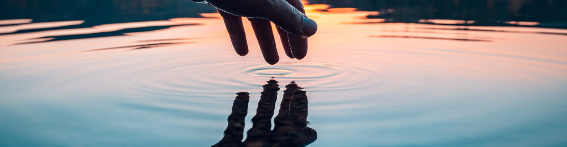 Finger touches surface of mountain lake. Hand reflection