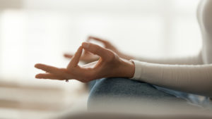 Close up peaceful woman sitting in lotus pose and meditating, practicing yoga at home, hands fingers view, calm girl controlling emotions, no stress, healthy lifestyle concept