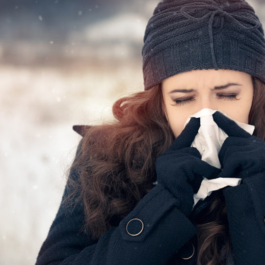 woman in hat and gloves outside in winter blowing her nose.
