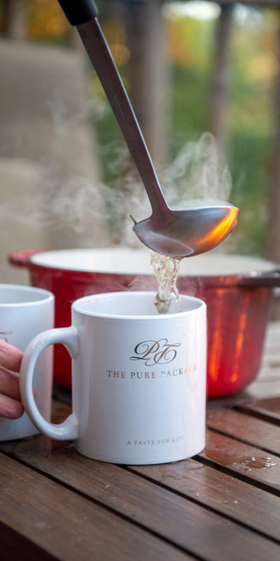Bone broth being poured into The Pure Package mugs