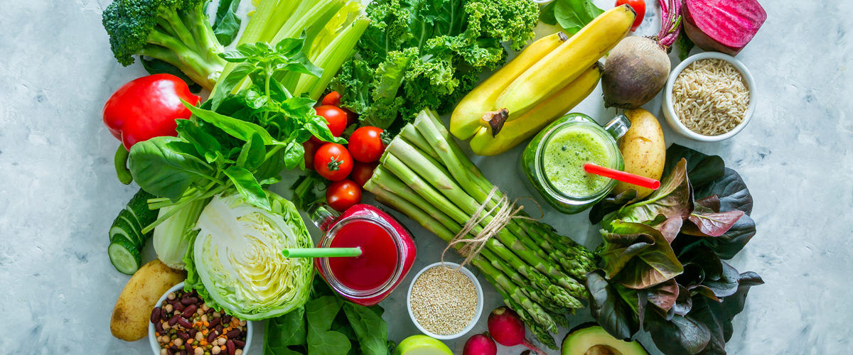 Lot's of fresh foods including fruits and vegetables on rustic background.
