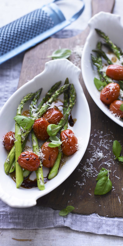Roasted Asparagus and Baby Tomatoes with Basil and Parmesan in white serving dishes